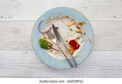 Overhead shot of an empty plate with leftovers from a meal on a white wooden backround