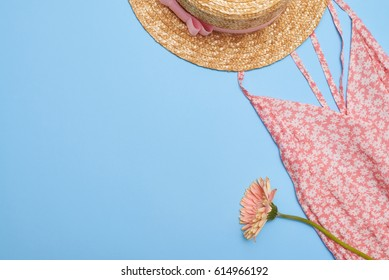 Overhead shot of a female summer outfit on blue desktop. Printed summer dress with straw hat on blue background