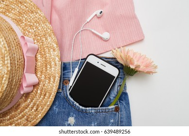 Overhead shot of feminine trendy fashion clothes on white background. Telephone and headphone lying in the pocket