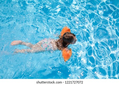 overhead shot of four years old blonde child with orange floater sleeves in arms, armbands, swimming in blue beautiful water of pool