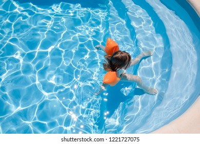 overhead shot of four years old blonde child with orange floater sleeves in arms, armbands, in blue beautiful water, relaxed, standing on stairs of swimming pool