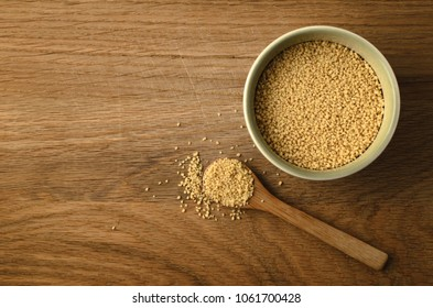 Overhead shot of green ceramic bowl and upturned wooden spoon filled with couscous. Some grains spill onto old oak wood surface background. Copy space to left.