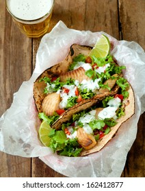 Overhead shot of grilled fish tacos on whole grain tortillas with a beer.
