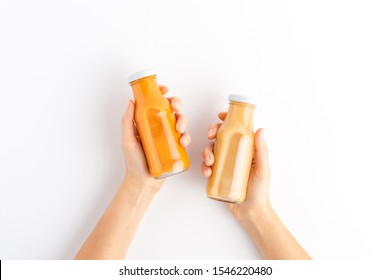 Overhead shot of woman's hands holding bottles of fruit and vegetable juices isolated on white background