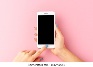 Overhead shot of woman's hands holding mobile phone with empty screen on pink background. Top view