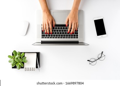 Overhead shot of woman's hands working on laptop on white table with accessories. Office desktop. Flat lay