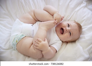 Overhead Shot Of Happy Baby Boy Lying On Parents Bed