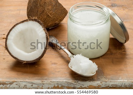 Overhead shot of a jar of coconut oil with a dessetspoon of oil  and a halved coconut to the left on a wooden background