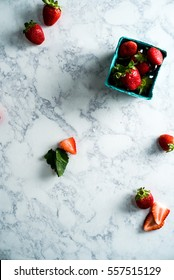 Overhead shot of juicy red strawberries with green tips in teal farmer's market carton on white marble surface with whole and sliced strawberries and a strawberry leaf on white marble surface.