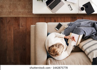 Overhead Shot Looking Down On Woman Working As Social Media Influencer At Home Lying On Sofa