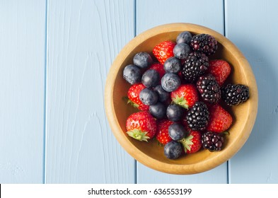 Overhead shot of mixed Summer berry fruits filling a wooden bowl on light blue painted wood planked table. Copy space to left.