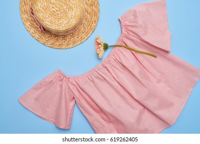 Overhead shot of an off-the-shoulder swing blouse with straw hat. Summer feminine outfit. Straw hat, blouse and flower on blue