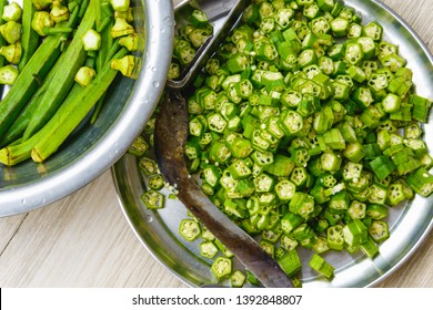 Overhead shot of okras and cut okras. A traditional nepalese knife on the plate.
