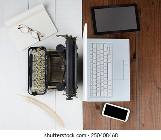Overhead shot of and old fashioned desk with typewriter and quill pen back-to-back with a modern set up with laptop computer, tablet and cell phone, (Phone and Tablet created in Photoshop - not real)