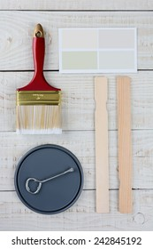 Overhead shot of  a paint can lid, opener, color samples, stir sticks and paint brush on a rustic wooden surface. Vertical format with copy space.