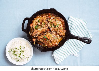 Overhead shot of pan-seared pork chops with tomatoes and green chiles in cast iron skillet served with white rice topped with fresh parsley on light blue linen.