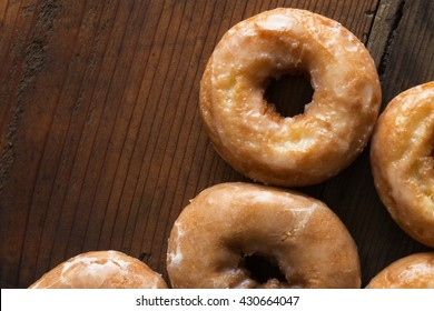 Overhead shot of plain cake donuts on a wood background. Close up shot.
