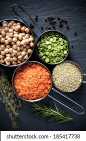 Overhead shot of pulses, chickpeas, lentils, Quinoa and black peppercorns against a stone surface with fresh herbs. Concept image for healthy or vegetarian cooking.