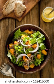 Overhead shot of quinoa salad with butternut squash and oil and vinegar dressing.