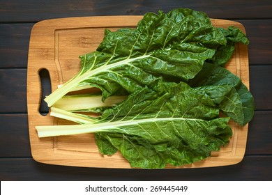 Overhead shot of raw chard leaves (lat. Beta vulgaris) on wooden board, photographed on dark wood with natural light
