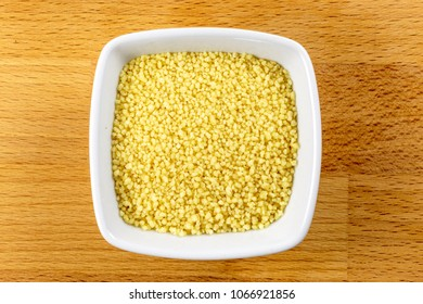 Overhead shot of raw couscous in a white bowl on a wooden background