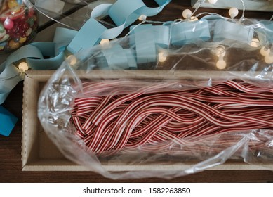 An overhead shot of red and white polkagris sticky candies or Swedish candy canes inside of a plastic paper
