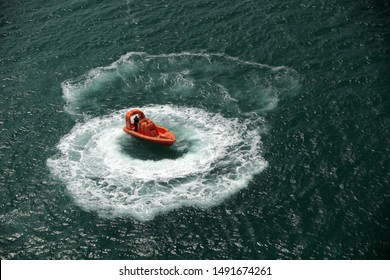 overhead shot of a rescue boat in ocean moving in a circle pattern