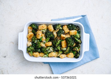 Overhead shot of rich green broccoli and roasted tater tots casserole topped with grated parmesan cheese and black pepper on light blue linen in simple white casserole dish on cream marble surface.