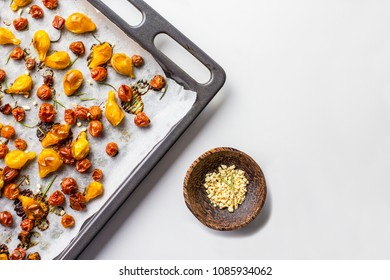 Overhead shot of roasted tomato with dried garlic in wooden bowl