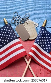 Overhead shot of a set of dog tags and two American flags on a red white blue patriotic table. Vertical format. Useful for 4th of July, Memorial Day and Veterans Day projects.