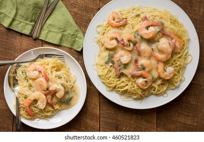 Overhead shot of shrimp scampi with angel hair pasta being served on a wooden table. Shown with green linen napkin.