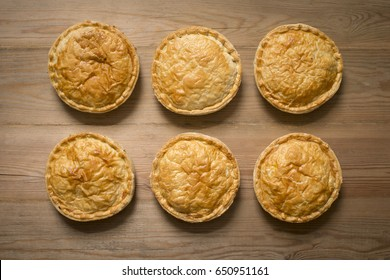 Overhead shot of six cooked whole meat pies on wooden surface