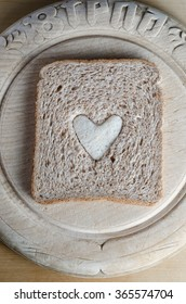 Overhead shot of a slice of brown bread with white bread heart in centre, on a round vintage bread board.