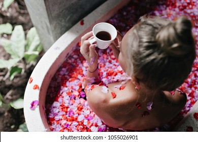 Overhead shot of spectacular woman with cup of hot beverage chilling in bath. Gorgeous blonde girl enjoying spa and looking at flower petals.