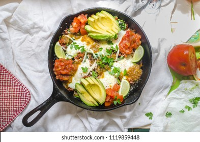 An overhead shot of a super tasty and spicy chorizo mexican breakfast skillet with avocado, red salsa, green salsa, eggs, tomatoes, lime slices and hash browns
