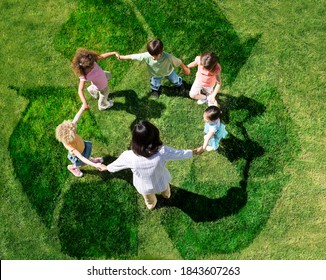 Overhead shot of teacher with five young students in a circle forming a human chain play on a green lawn outdoors with overlay of recycle symbol.