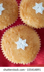 Overhead shot of three vanilla cupcakes in paper cases on red paper napkin, decorated with sprinkled white icing sugar in the shape of stars.