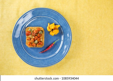 Overhead shot of toast with tomato on blue plate empty space