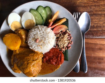 Overhead shot of traditional Malay nasi lemak dish on a wooden table