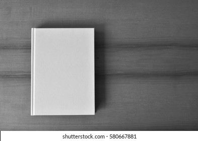 Overhead shot of a white blank book on wooden table. Black and white photo