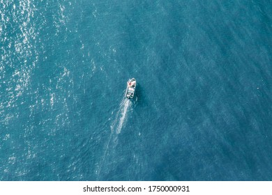 An overhead shot of a white boat in pure blue water during a sunny day- perfect wallpaper or background