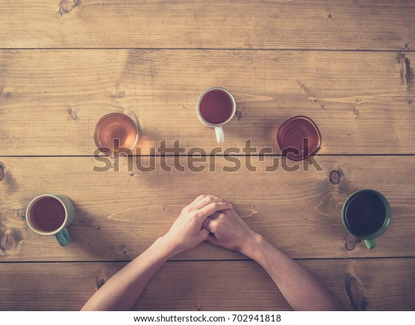 Overhead shot of a woman resting her arms on a table with selection of cups with tea