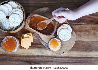 Overhead shot of a woman's hand preparing Water cracker, cheddar cheese and homemade savory Salted Vanilla Cantaloupe jam appetizers.