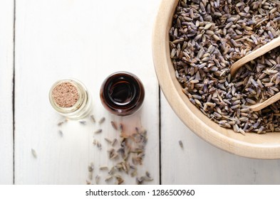 Overhead shot of a wooden bowl filled with dried lavender and two glass vials filled with oils. Further buds scattered on white wood planked table.