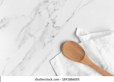 Overhead Shot of a Wooden Mixing Spoon on a White Linen Napkin on a White Marble Kitchen Counter with Room for Text.