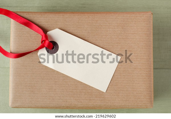 Overhead shot of a wrapped brown paper gift package on a green table. Topped with a parcel tag and red ribbon.  The blank label faces upwards to provide copy space for a message.