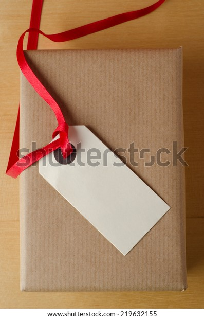 Overhead shot of a wrapped brown paper gift package on wood veneer table. Topped with a parcel tag and red ribbon, the blank label faces upwards to provide copy space for a message.