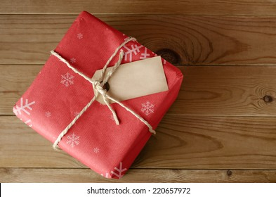 Overhead shot of a wrapped red Christmas parcel with snowflake pattern, tied with string.  Blank label faces upwards to provide copy space.  Set on an old, worn wooden table.