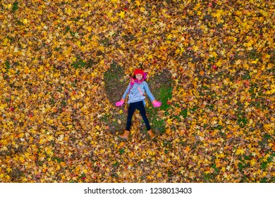 overhead shot of a young girl making leaf angels in autumn foliage
