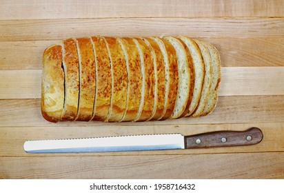 Overhead sliced bread with read knife serrated edge. On wooden cutting board background.